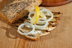 Sprats, smoked, salad, lemon, onions, whole wheat bread Stock Image