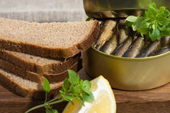 Sprats in a tin and coarse rye bread Royalty Free Stock Photography