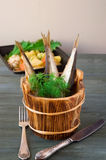 Sprats in wooden barrels with greens on a background of potatoes Royalty Free Stock Images