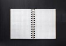 Sprawdzać notatnik na czarnym drewnie Obrazy Royalty Free