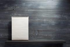 Sprawdzać notatnik przy szelfowym drewnem Fotografia Stock