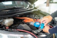 Sprawdza samochodowego klimatyzacji chłodziwo podładowywa obrazy stock