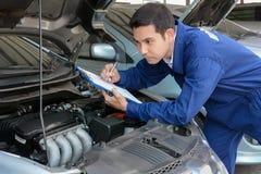 Sprawdza samochodowego silnika auto mechanik lub technik () zdjęcia royalty free