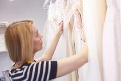 Sprawna żeńska krawcowa wybiera modela ślubna suknia fotografia stock