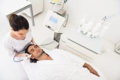 Sprawnego cosmetologist masowania męska twarz z wyposażeniem Zdjęcia Royalty Free