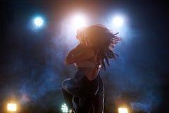 Sprawni tancerze wykonuje w ciemnym pokoju pod porozumiewają się światło i dymią Zmysłowa para wykonuje artystycznego fotografia stock