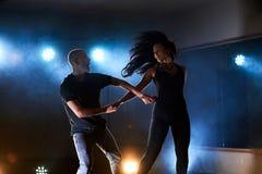 Sprawni tancerze wykonuje w ciemnym pokoju pod porozumiewają się światło i dymią Zmysłowa para wykonuje artystycznego zdjęcie stock