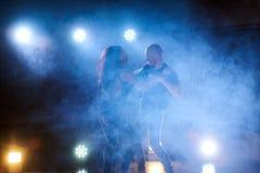 Sprawni tancerze wykonuje w ciemnym pokoju pod porozumiewają się światło i dymią Zmysłowa para wykonuje artystycznego obrazy royalty free