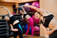 Sprawność fizyczna, szkolenie, aerobiki i ludzie pojęć, Piękne kobiety ćwiczy aerobiki w sprawność fizyczna klubie zdjęcia stock