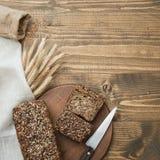 Sprawność fizyczna chleb Bochenek świeży nieociosany cały posiłku żyta chleb, pokrajać na drewnianej desce, wiejski karmowy tło O Zdjęcia Stock