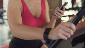 Sprawność fizyczna gadżety, szczupła kobieta z wristband jazdą na stacjonarnym rowerze w gym zbiory wideo