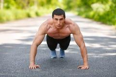 Sprawność fizyczna mężczyzna podnosi, plenerowy ćwiczyć pcha Mięśniowy męski szkolenie na miasto parku Zdjęcia Stock