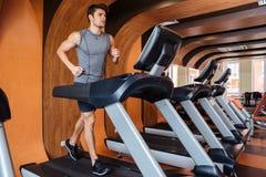 Sprawność fizyczna mężczyzna pracujący out i biegający na karuzeli w gym Obraz Stock