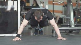 Sprawność fizyczna mężczyzna robi Ups ćwiczenia intensywnemu szkoleniu w gym zbiory