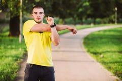 Sprawność fizyczna mężczyzna rozciągania ręki ramię przed plenerowym treningiem Sporty męska atleta w miastowy parkowy rozgrzewko zdjęcia royalty free