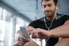 Sprawność fizyczna mężczyzna używa smartphone w gym obraz stock