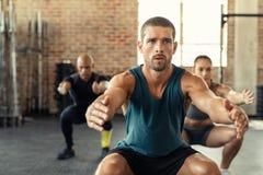 Sprawność fizyczna mężczyzny kucanie z klasą przy gym fotografia stock