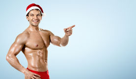 Sprawność fizyczna seksowny Święty Mikołaj, przedstawienie palec wskazujący i uśmiech, na błękicie zdjęcie royalty free
