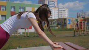 Sprawność fizyczna, sport, szkolenie, park i stylu życia pojęcie, - uśmiechnięta kobieta robi Ups na ławce outdoors zbiory