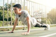 Sprawność fizyczna sporta mężczyzna mody sportswear robi joga sprawności fizycznej ćwiczeniu w ulicie Dysponowany młody azjatykci Zdjęcia Royalty Free
