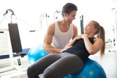 Sprawność fizyczna trener Pomaga kobiety na ćwiczenie piłce obraz stock