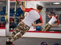 Sprawność fizyczna trener pracuje z zawieszenie patkami zdjęcie royalty free