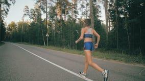 Sprawność fizyczna trening młode kobiety bieżące Żeński biegacz jogging na parkowej drodze Sprawność fizyczna trening Slowmotion zbiory