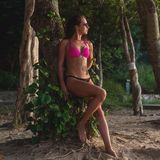 Sprawności fizycznej żeńskiej brunetki wzorcowy jest ubranym bikini i okulary przeciwsłoneczni opiera przeciw drzewnemu mieniu je zdjęcia royalty free