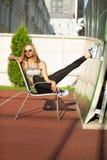 Sprawności fizycznej blondynki dziewczyna ubierał w sportów ubraniach, pozuje przy tenn zdjęcie stock