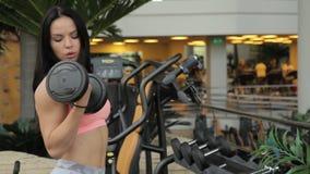 Sprawności fizycznej dama robi bicepsów dumbbells kędziorom podczas gdy stojący w gym zbiory wideo