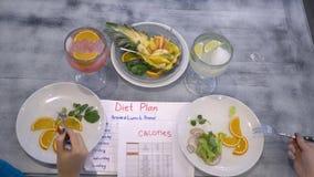 Sprawności fizycznej dieta, dziewczyny siedzi przy stołem z kaloria stołem i dieta planem je warzywa i owoc od talerzy zdjęcie wideo