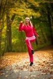 Sprawności fizycznej dysponowanej kobiety blond dziewczyna robi ćwiczeniu w jesiennym parku. Sport. Zdjęcie Royalty Free