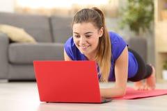 Sprawności fizycznej dziewczyna ćwiczy dopatrywanie na kreskowych wideo w domu fotografia stock