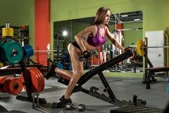 Sprawności fizycznej dziewczyna wykonuje ćwiczenie z dumbbells zdjęcia stock