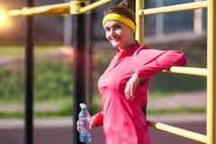 Sprawności fizycznej i treningu pojęcia Szczęśliwa ono Uśmiecha się Kaukaska Żeńska atleta w Fachowym stroju Pozuje Z bidonem Bli Obrazy Royalty Free