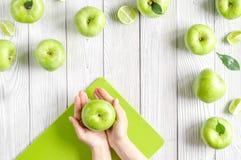Sprawności fizycznej jedzenie z zielonymi jabłkami w ręce na białego tła odgórnym widoku Zdjęcie Royalty Free