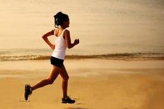 Sprawności fizycznej kobieta jogging przy wschodu słońca, zmierzchu plażą/ Obrazy Stock