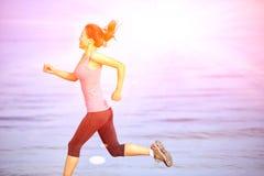 sprawności fizycznej kobieta jogging przy wschodu słońca, zmierzchu plażą/ Obraz Royalty Free