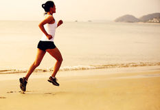 Sprawności fizycznej kobieta jogging przy wschodu słońca, zmierzchu plażą/ Zdjęcia Royalty Free