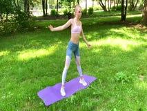 Sprawności fizycznej kobieta robi ćwiczeniu na zielonym gazonie zdjęcie wideo