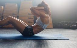 Sprawności fizycznej kobieta robi abs chrupnięciom Fotografia Stock