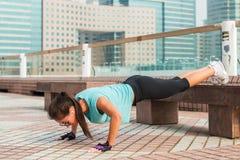 Sprawności fizycznej kobieta robi ciekom wynosił Ups na ławce w mieście Sporty dziewczyna ćwiczy outdoors obrazy stock