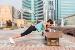 Sprawności fizycznej kobieta robi ciekom wynosił Ups na ławce w mieście Sporty dziewczyna ćwiczy outdoors zdjęcia royalty free