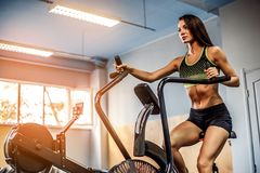 Sprawności fizycznej kobieta używa lotniczego rower dla cardio treningu przy crossfit gym Zdjęcia Royalty Free