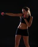 Sprawności fizycznej kobieta uderza pięścią czerwone stażowe rękawiczki i jest ubranym Fotografia Stock