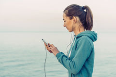 Sprawności fizycznej kobieta wybiera muzykę Zdjęcia Royalty Free