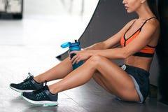 Sprawności fizycznej kobieta z butelką woda Aktywna dziewczyna quenches pragnienie, trening Fotografia Royalty Free