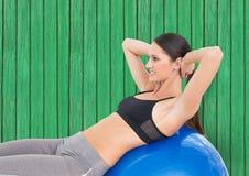 sprawności fizycznej kobieta z dużą piłką z zielonym drewnianym tłem Fotografia Stock