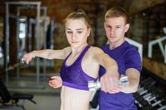Sprawności fizycznej kobiety i ogłoszenie towarzyskie trenera mężczyzna z ciężaru stażowym wyposażeniem obraz royalty free