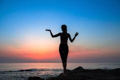 Sprawności fizycznej kobiety sylwetka na morzu podczas zadziwiającego zmierzchu Zdjęcie Stock